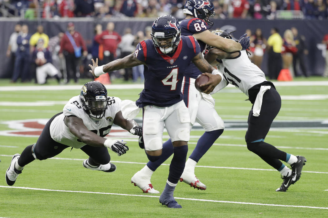 Houston Texans quarterback Deshaun Watson (4) runs from the reach of Jacksonville Jaguars defensive tackle Abry Jones (95) during the second half of an NFL football game, Sunday, Dec. 30, 2018, in ...