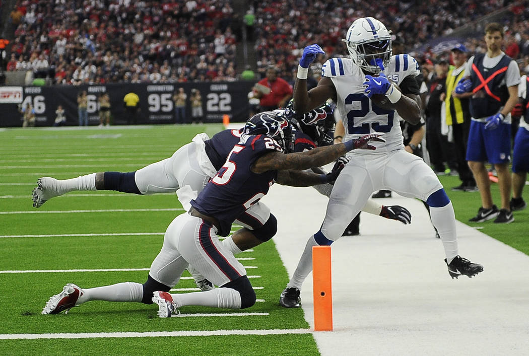 Indianapolis Colts running back Marlon Mack, left, is hit by Houston Texans inside linebacker Benardrick McKinney, back left, and strong safety Kareem Jackson (25) during the first half of an NFL ...