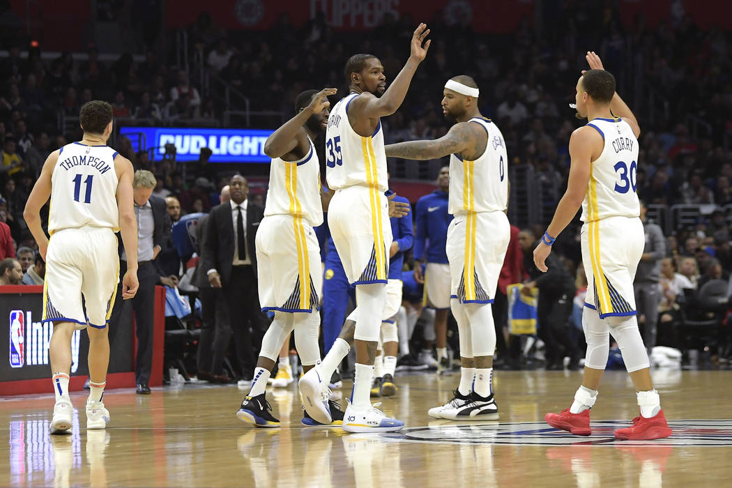 Golden State Warriors' Klay Thompson, Draymond Green, Kevin Durant, DeMarcus Cousins and Stephen Curry, from left, celebrate during the second half of the team's NBA basketball game against the Lo ...