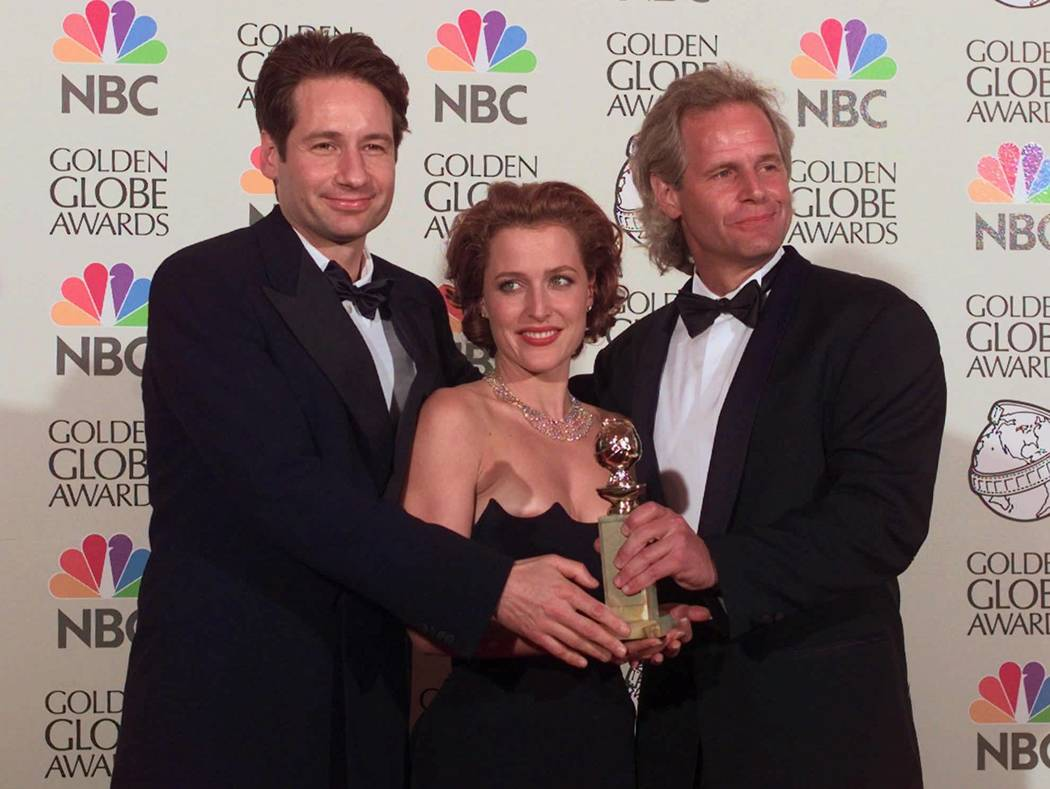 """X-Files"" co-stars David Duchovny, left, and Gillian Anderson pose with creator Chris Carter after winning the award for Best Dramatic Television Series at the 55th Annual Golden Globe A ..."