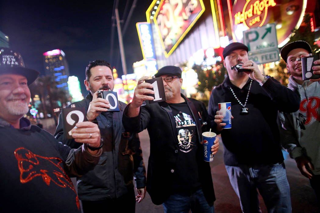 Dave Holtgreven, from left, Angelo Guerrero, Tyrone Greene, Leroy Washington, and Jsutin Walters, all friends from Tacoma, Washington, take shots on the Strip in Las Vegas, Monday, Dec. 31, 2018. ...
