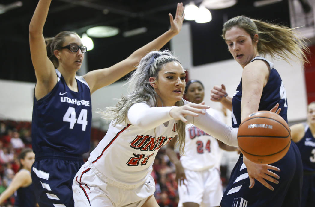 UNLV Lady Rebels forward/center Katie Powell (21) goes for a loose ball against Utah State Aggies forward Taylor Franson, right, during the first half of a basketball game at the Cox Pavilion in L ...