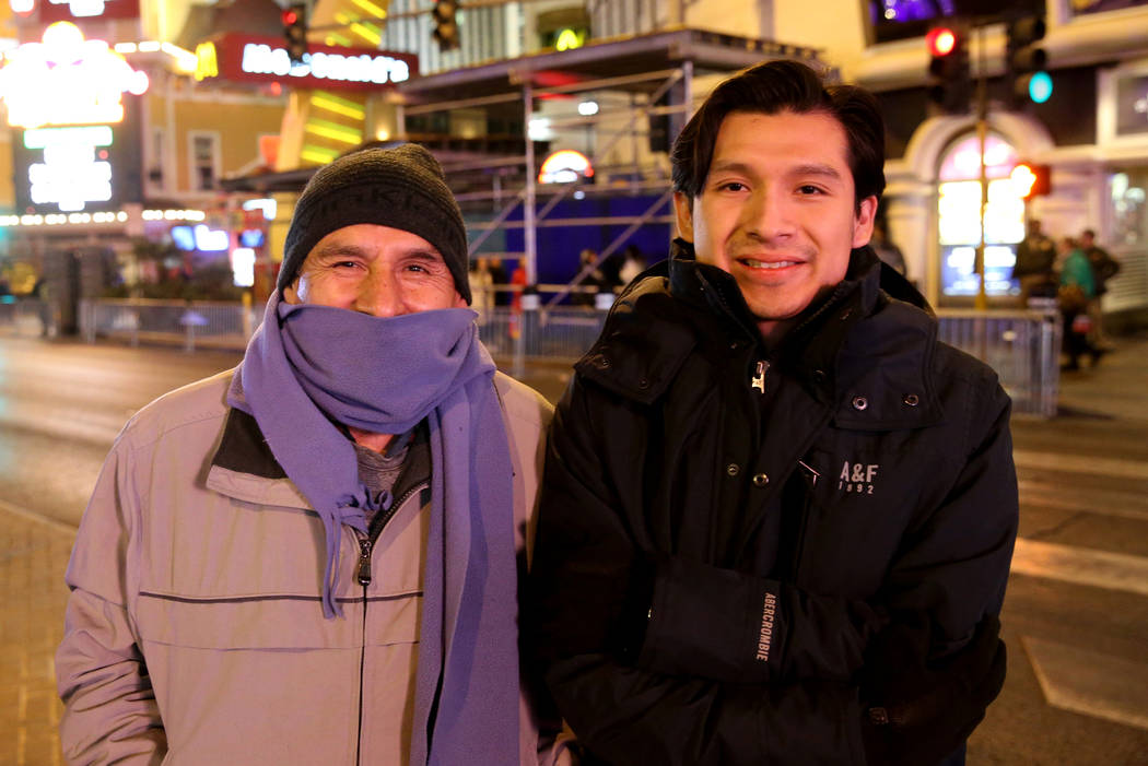 Jaime Solano, left, and his son Kenneth Solano stay warm on the north Strip on New Year's Eve in Las Vegas Monday, Dec. 31, 2018. K.M. Cannon Las Vegas Review-Journal @KMCannonPhoto
