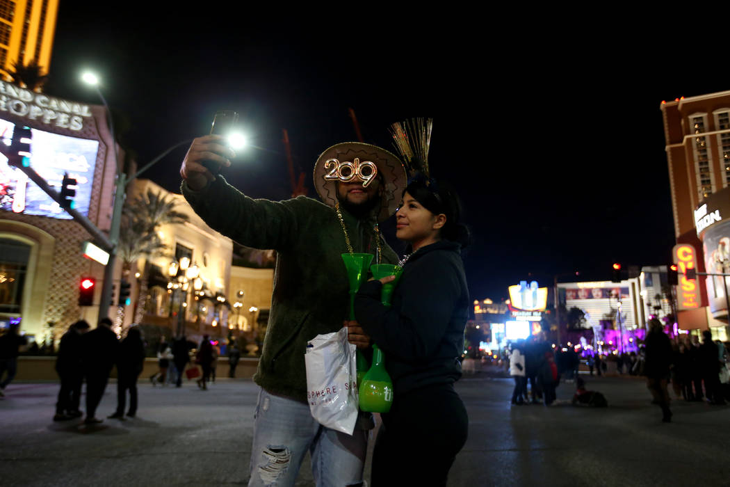 Justin Bolton, 21, and Yvette Vallejas, 22, of Everett, Wash. take a selfie in the intersection of Las Vegas Boulevard and Sands Avenue on New Year's Eve in Las Vegas Monday, Dec. 31, 2018. K.M. C ...