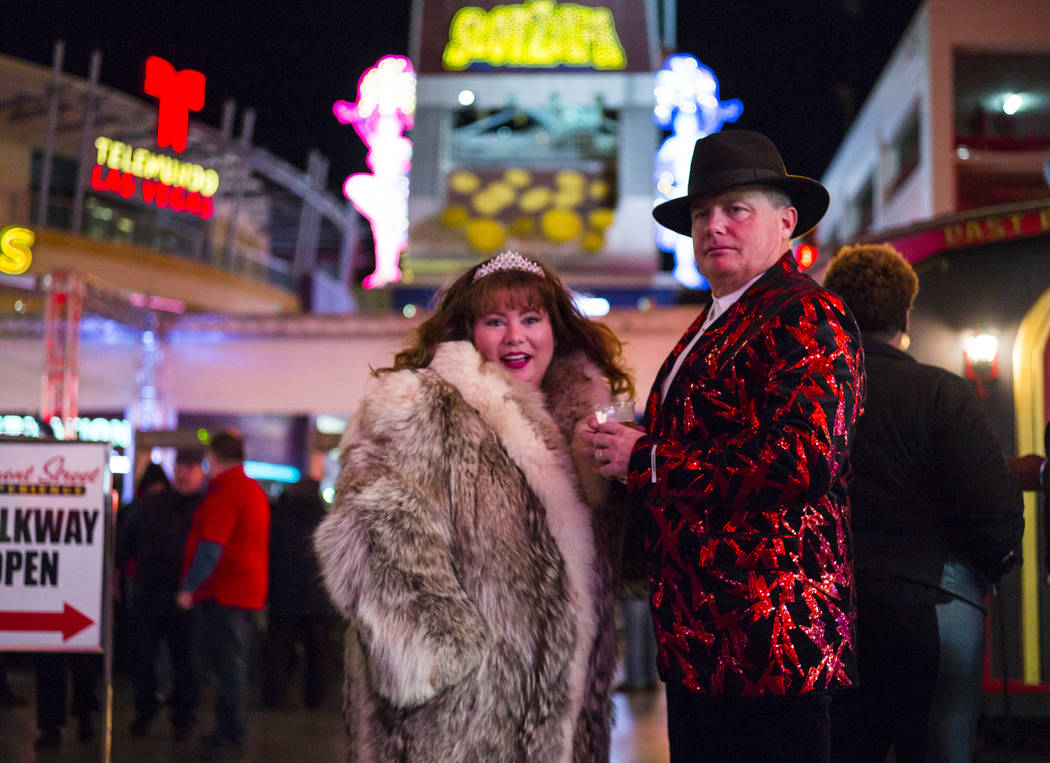 Jeanie Arnold, left, and Shane Arnold, both of Phoenix, take in the sights of the Fremont Street Experience as New Year's Eve revelers gather in downtown Las Vegas on Monday, Dec. 31, 2018. Chase ...