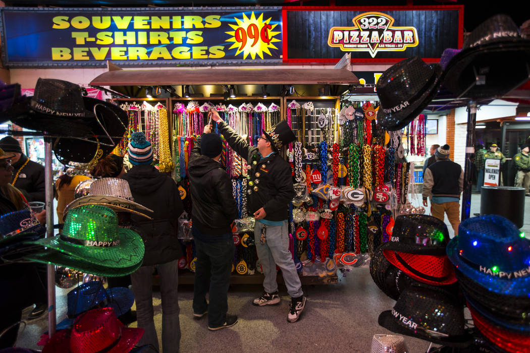 Vendor Rueben Ascencio, right, looks through apparel as New Year's Eve revelers gather at the Fremont Street Experience in downtown Las Vegas on Monday, Dec. 31, 2018. Chase Stevens Las Vegas Revi ...