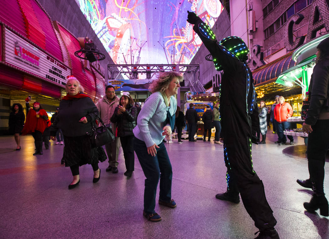Karen Johnston of Colo., center, dances with a costumed entertainer as New Year's Eve revelers gather at the Fremont Street Experience in downtown Las Vegas on Monday, Dec. 31, 2018. Chase Stevens ...