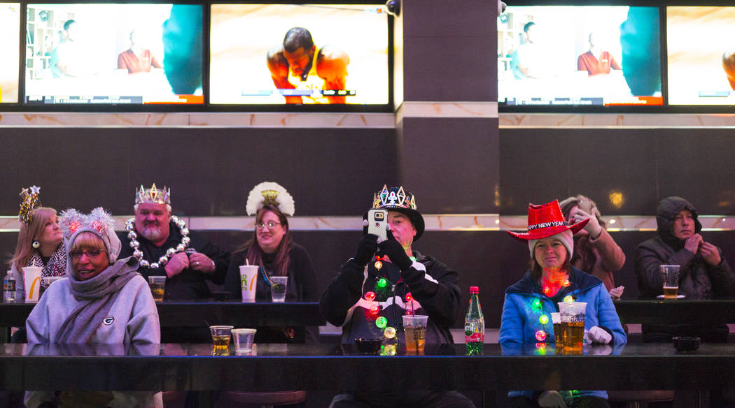 New Year's Eve revelers take in the sights of the Fremont Street Experience from a bar area in downtown Las Vegas on Monday, Dec. 31, 2018. Chase Stevens Las Vegas Review-Journal @csstevensphoto