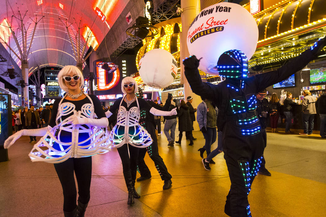 Costumed performers Kylie Miller, left, and Maraiya Claudio, center, entertain the crowd as New Year's Eve revelers gather at the Fremont Street Experience in downtown Las Vegas on Monday, Dec. 31 ...