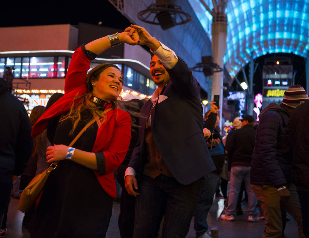 Alisha Hendrickson, left, and Richard Wright, both of Humboldt County, Calif., dance as New Year's Eve revelers gather at the Fremont Street Experience in downtown Las Vegas on Monday, Dec. 31, 20 ...