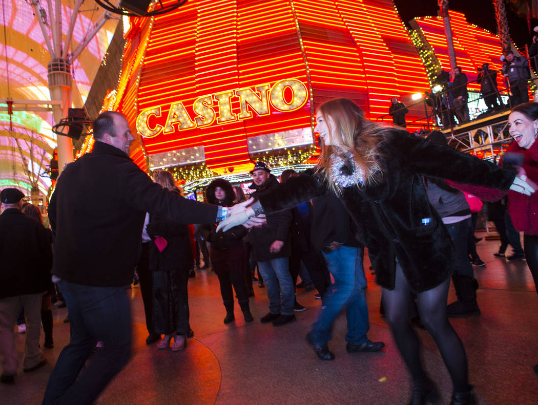 Robert Drye of Las Vegas, left, dances with Anya Dubiel of London as New Year's Eve revelers gather at the Fremont Street Experience in downtown Las Vegas on Monday, Dec. 31, 2018. Chase Stevens L ...