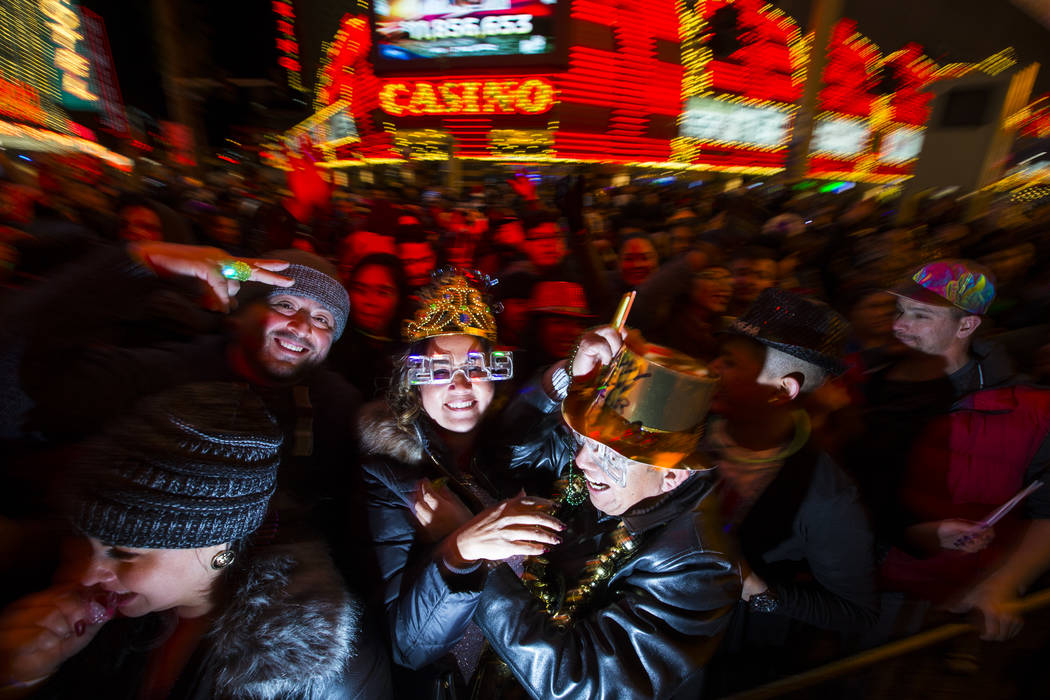 Maria Elena Sanchez, center left, and Anselmo Garcia cheer during the final minutes of 2018 as New Year's Eve revelers gather at the Fremont Street Experience in downtown Las Vegas on Monday, Dec. ...