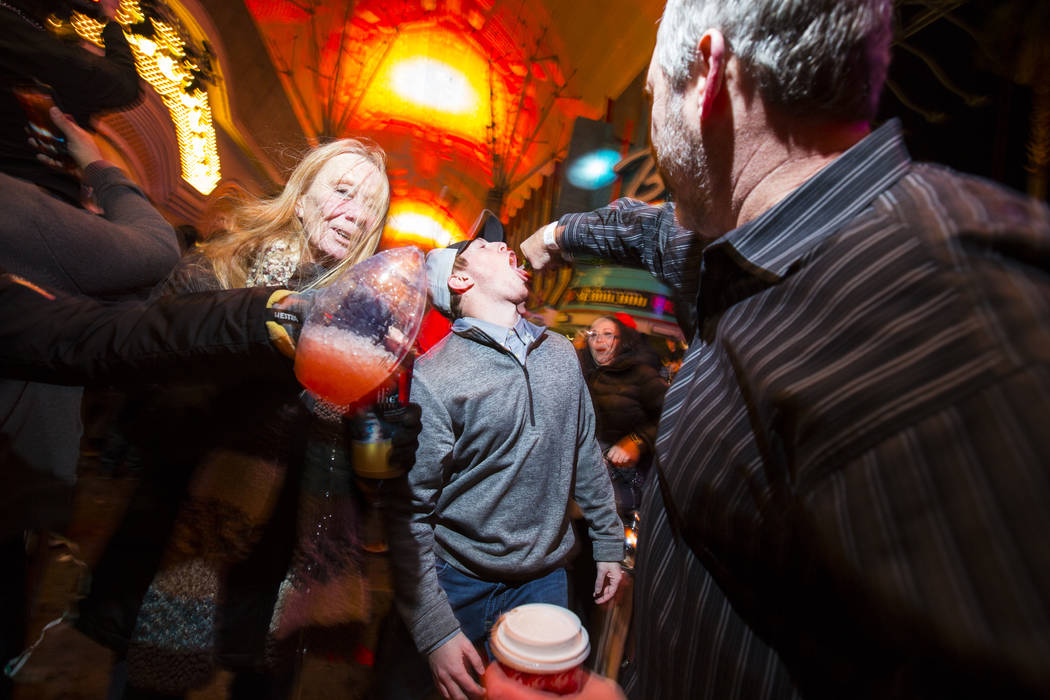 Elijah Poulos, of Flagstaff, Ariz., right, shares a bottle of champagne with Joseph Montellano of Phoenix, center, while celebrating the new year at the Fremont Street Experience in downtown Las V ...