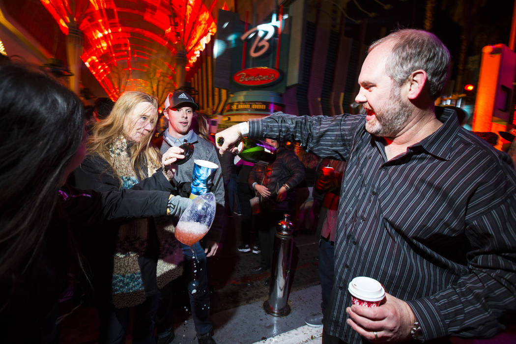 Elijah Poulos, of Flagstaff, Ariz., right, shares a bottle of champagne with revelers while celebrating the new year at the Fremont Street Experience in downtown Las Vegas on Tuesday, Jan. 1, 2019 ...