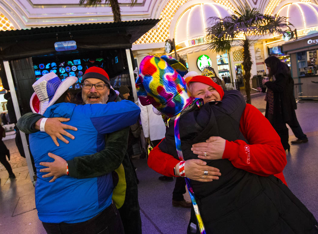 James Melbrow, second from left, of Henderson, and Wendy Beckers, right, of Vancouver, Canada, offer free hugs to strangers as New Year's Eve revelers gather at the Fremont Street Experience in do ...