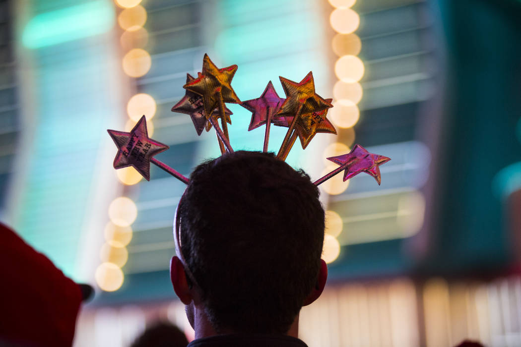 A New Year's Eve reveler wears a styled headpiece as people gather at the Fremont Street Experience in downtown Las Vegas on Monday, Dec. 31, 2018. Chase Stevens Las Vegas Review-Journal @cssteven ...