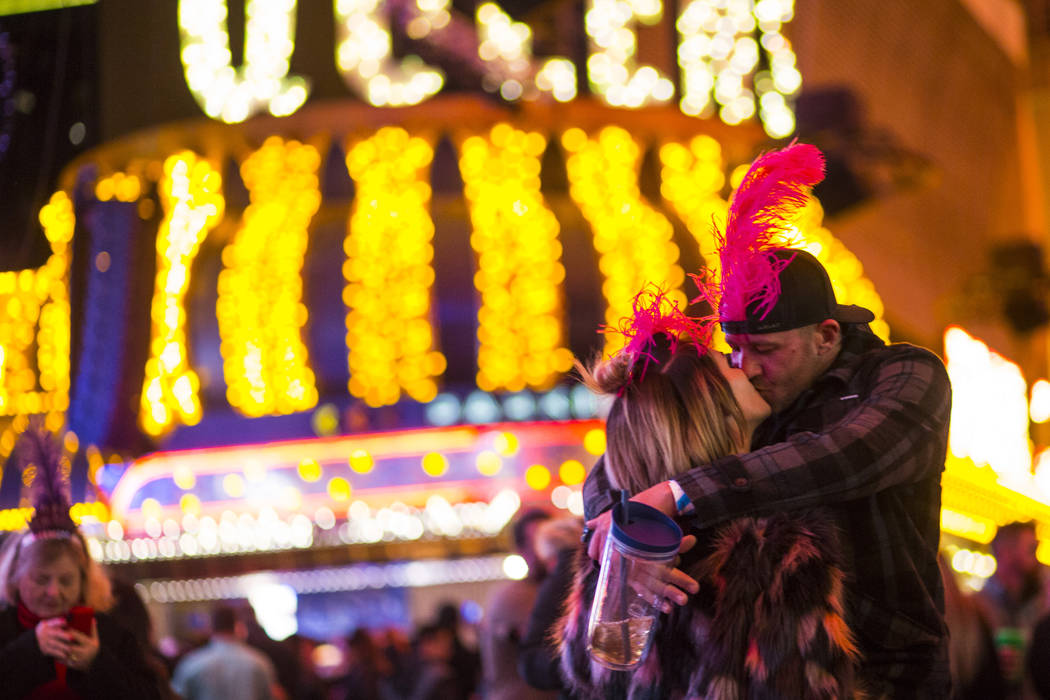 A couple shares a kiss as New Year's Eve revelers gather at the Fremont Street Experience in downtown Las Vegas on Monday, Dec. 31, 2018. Chase Stevens Las Vegas Review-Journal @csstevensphoto