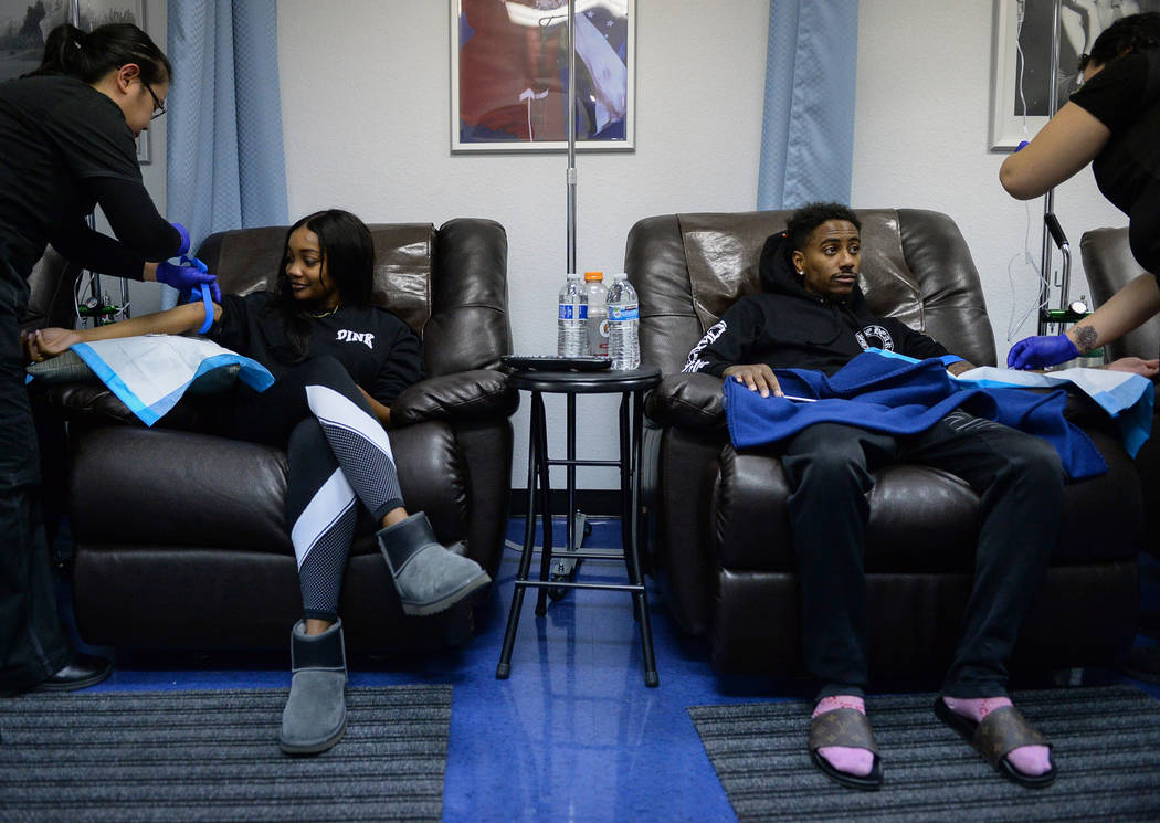 Shelbi Williams, left, and Daryl Johnson from Washington D.C. sit as they receive treatment at Hangover Heaven in Las Vegas, Tuesday, Jan. 1, 2019. Caroline Brehman/Las Vegas Review-Journal