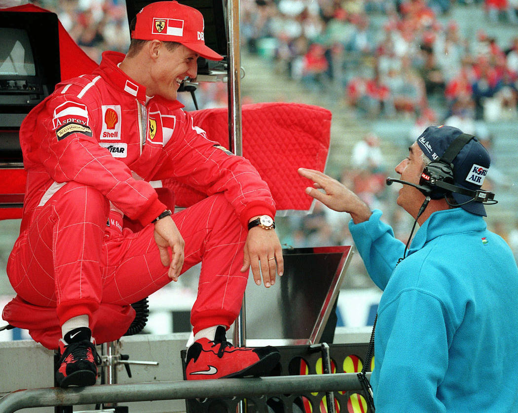 In this July 25, 1997, file photo, Germany's Michael Schumacher, left, of the Ferrari team, shares a joke with Benetton chief Flavio Briatore, right, at the start of the first free practice sessio ...
