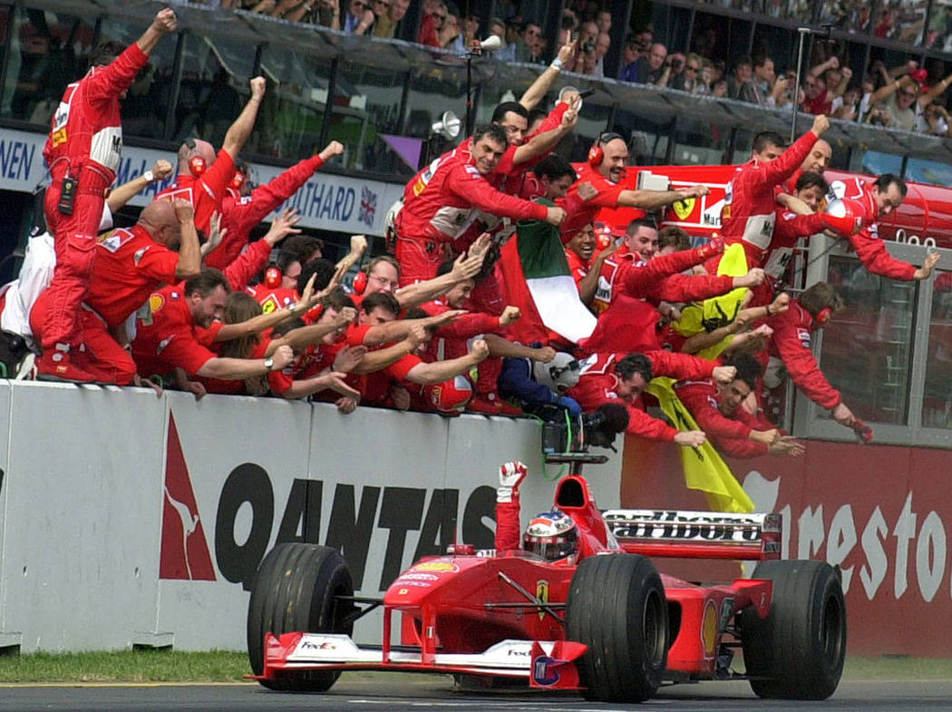 In this March 12, 2000, file photo, Ferrari's F1 driver Michael Schumacher, of Germany, is cheered by his pit crew as he heads for the finish line to win the Australian Grand Prix auto race in Mel ...