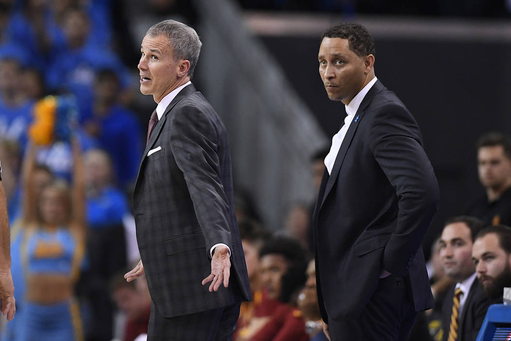 Southern California head coach Andy Enfield, left, talks to officials as assistant coach Tony Bland stands behind him during the second half of an NCAA college basketball game against UCLA, Saturd ...