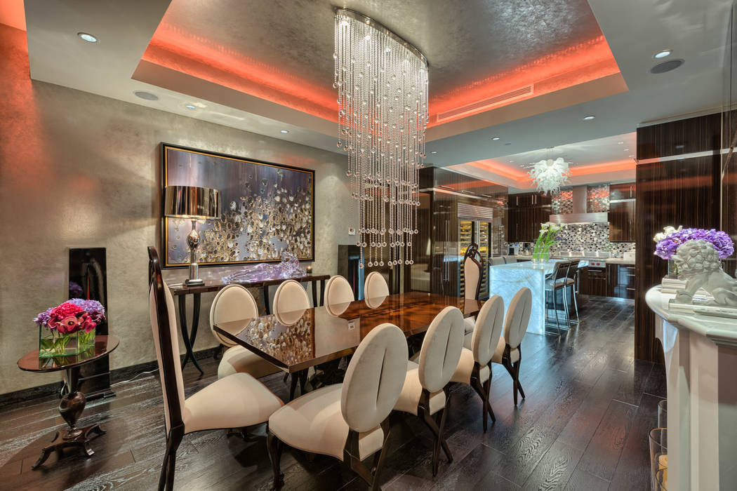 Luxury Estates International A custom chandelier by designer Todd Rugee cascades down from the coffered ceiling, creating a stunning focal point for the formal dining.
