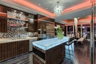The kitchen features professional-grade appliances, custom stainless steel hood, Murano blown glass chandelier, white diamond quartzite counters contrasted by dark artisan ebony tiger veneer cabin ...