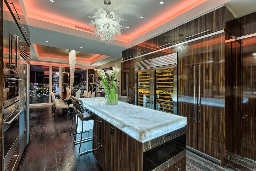 Luxury Estates International The kitchen features professional-grade appliances, custom stainless steel hood, Murano blown glass chandelier, white diamond quartzite counters contrasted by dark ar ...