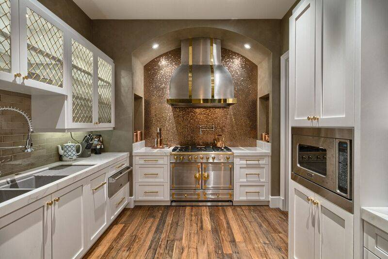 The kitchen's solid wood custom cabinetry accented with imported polished brass handles and custom grates provide a refined aesthetic. (Award Realty)