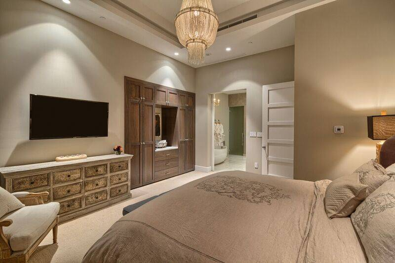 The main master includes a walk-in closet and a unique custom barn door master bath entry. (Award Realty)