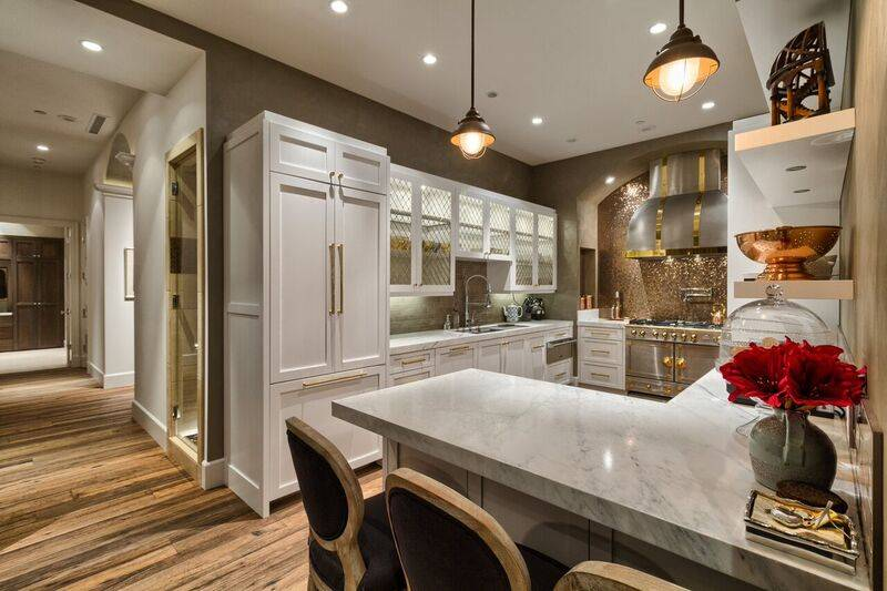 The white gourmet kitchen captures the European essence with an imported French La Cornue gas stove accentuated by a copper penny tile backsplash and custom stainless steel hood. (Award Realty)