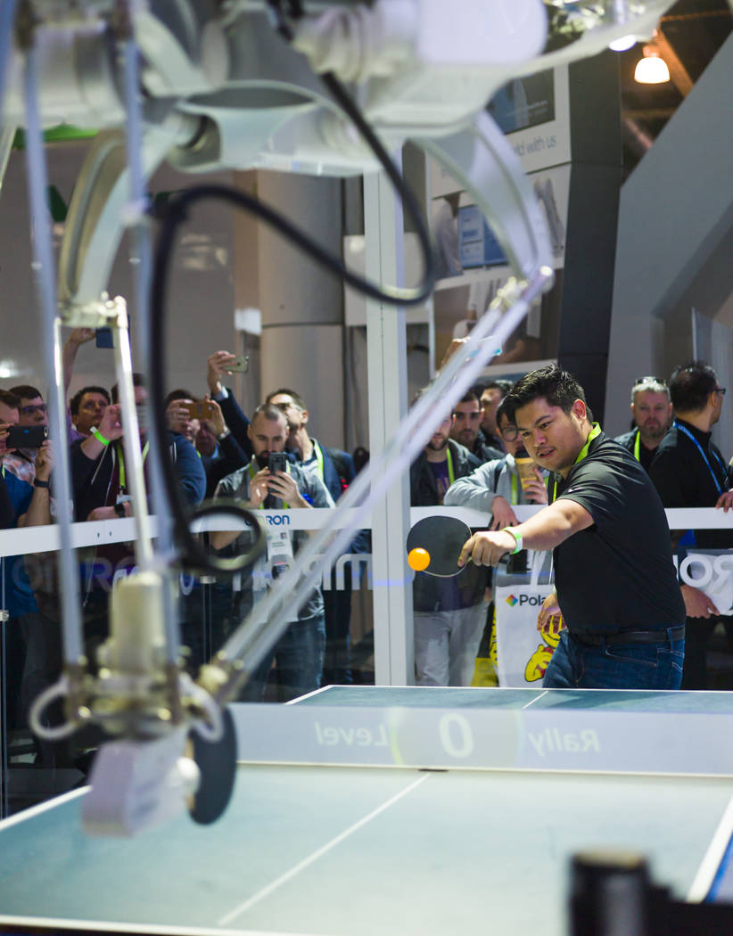 "Jordan Alfafara of Las Vegas plays a game of ping-pong against ""Forpheus,"" a robot created by Japanese company Omron, during CES at the Las Vegas Convention Center in Las Vegas on Friday ..."