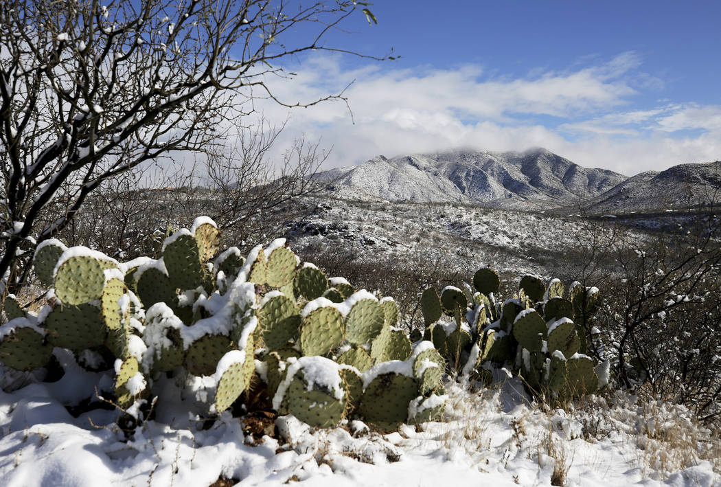 The Empire Mountains emerge from cloud cover after the second round of winter storms brought snowfall to the surrounding metro Tucson area and southeast Arizona, Jan. 2, 2019, south of Vail, Ariz. ...
