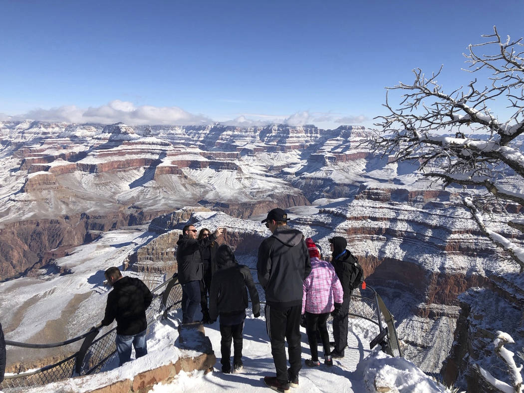 In this Tuesday, Jan. 1, 2019, photo, tourists look at and take photos of a snow-covered Grand Canyon, in Arizona. A winter storm has covered cactus with snow in parts of the American Southwest as ...