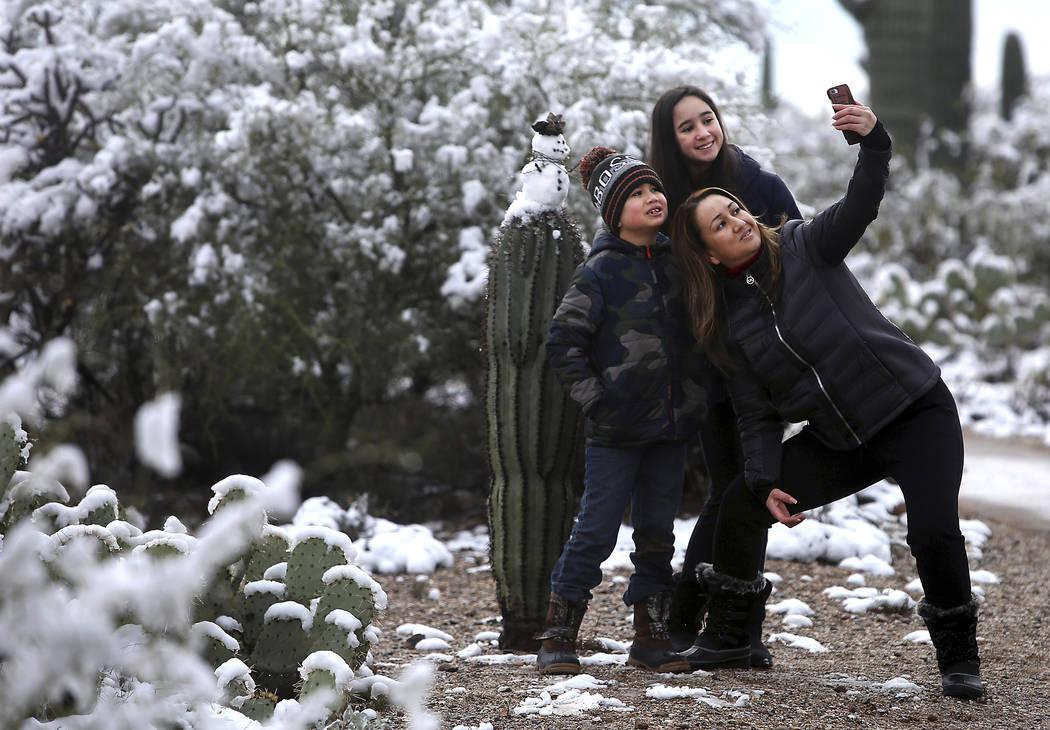 """It's the first time we've seen snow the desert,"" says Mayra Vasquez who brought Valeria Luzania, 11, and MarcoDario Luzania, 8, to Saguaro National Park East on January 02, 2019. The ki ..."