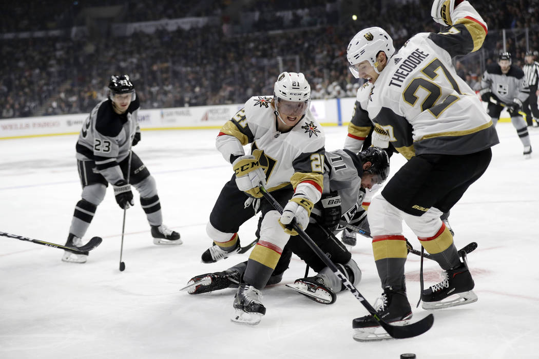 Vegas Golden Knights' Cody Eakin (21) becomes entangled with Los Angeles Kings' Anze Kopitar (11) and teammate Shea Theodore (27) during the second period of an NHL hockey game Saturday, Dec. 29, ...