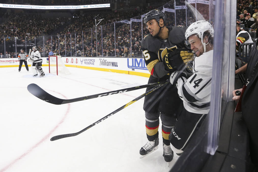 Los Angeles Kings left wing Brendan Leipsic (14) takes a hit from Golden Knights right wing Ryan Reaves (75) during the first period of an NHL hockey game at T-Mobile Arena in Las Vegas on Tuesday ...