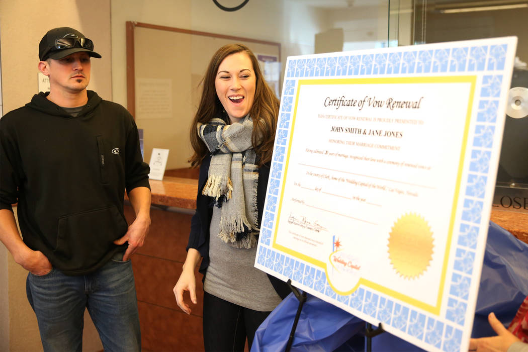 Jared Duval, left, and his wife, Brooke Siegert, of Still Water, Minn., assist in the unveiling of the new wedding vow renewal certificate during a press conference at the Marriage License Bureau ...