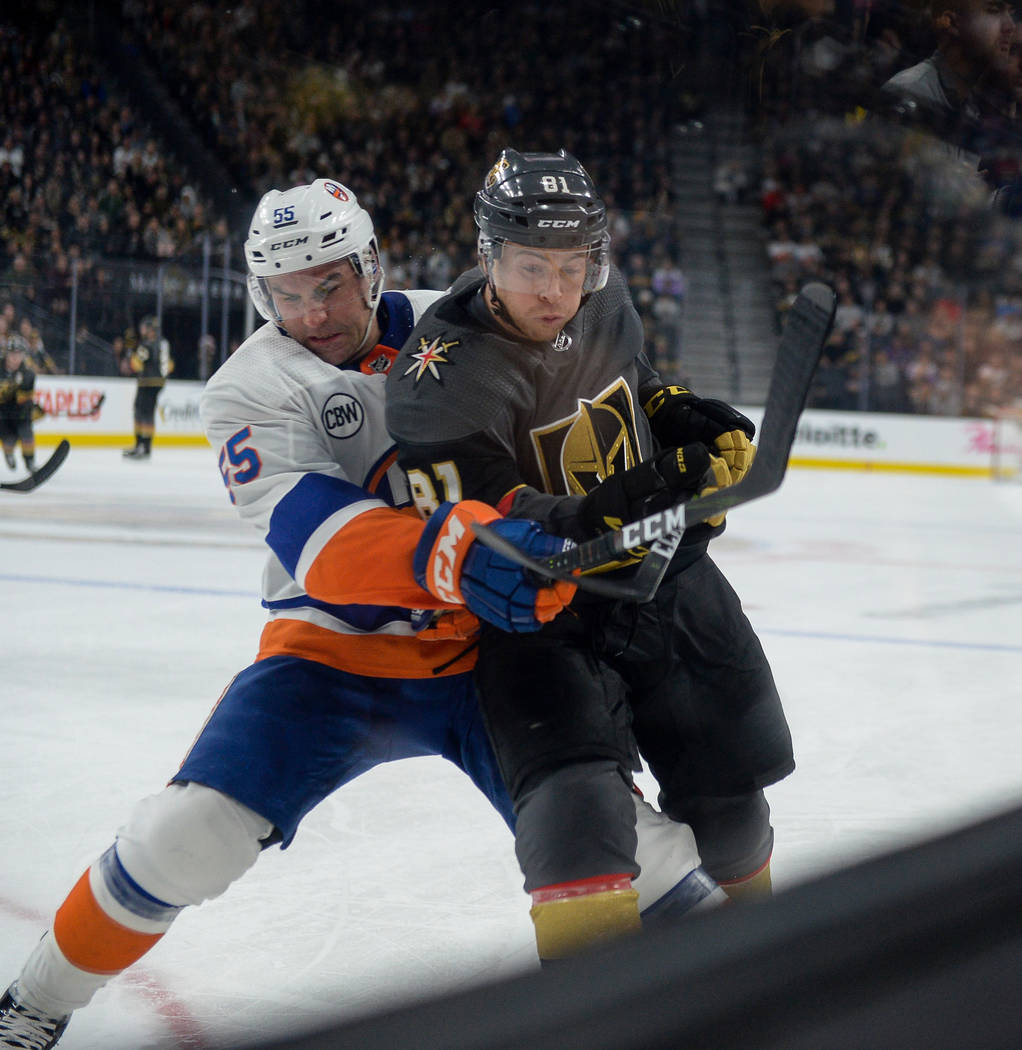 New York Islanders defenseman Johnny Boychuk (55) and Vegas Golden Knights center Jonathan Marchessault (81) fight for the puck during the first period of an NHL hockey game at T-Mobile Arena in L ...