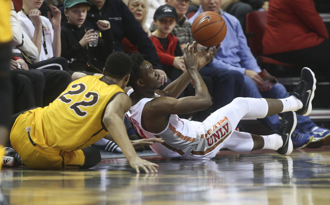 UNLV Rebels forward Joel Ntambwe (24) gets possession of a loose ball against Wyoming Cowboys forward Brandon Porter (22) during the first half of a basketball game at the Thomas & Mack Center ...