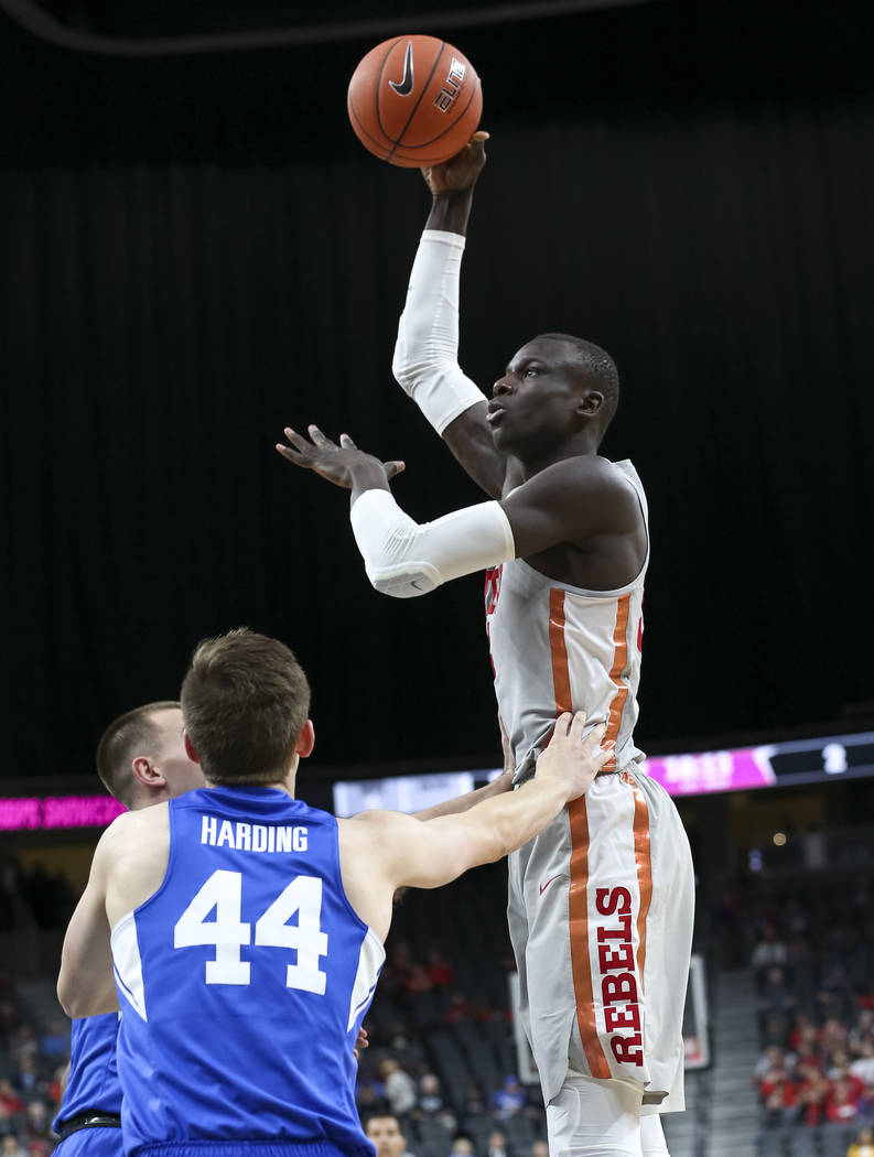 UNLV Rebels forward Cheikh Mbacke Diong (34) takes a shot over Brigham Young Cougars guards Connor Harding (44) and Nick Emery (4) during the first half of an NCAA college basketball game at T-Mob ...