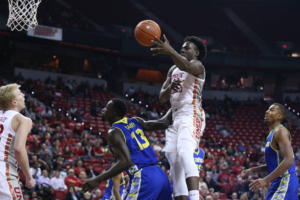 UNLV Rebels forward Jonathan Tchamwa Tchatchoua (30) makes a pass to guard Trey Woodbury (22) under pressure from San Jose State Spartans center Oumar Barry (13) in the first half of the basketbal ...