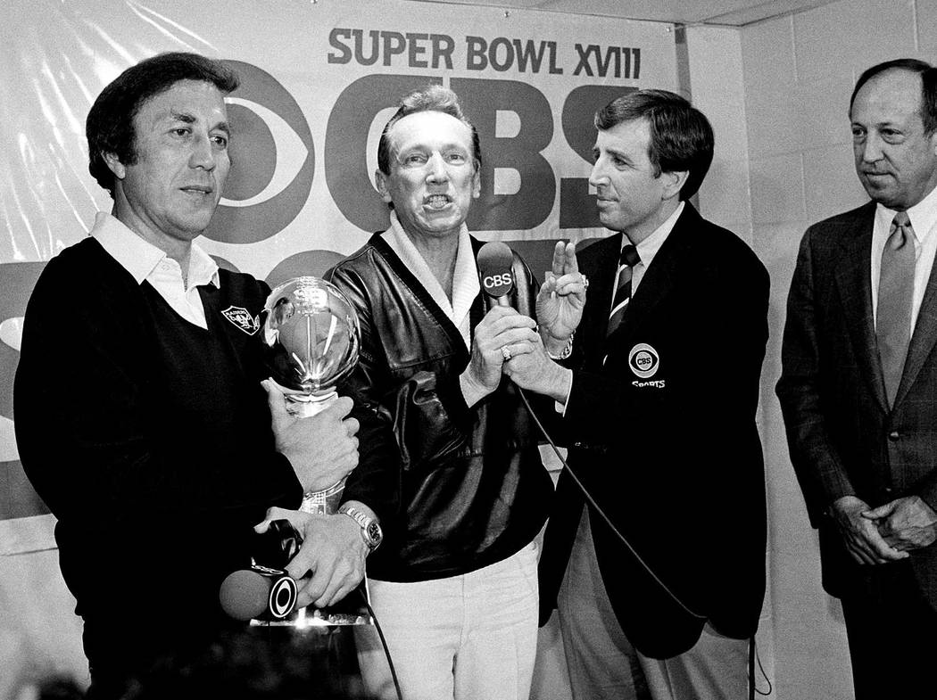 In this Jan. 23, 1984, file photo, Oakland Raiders coach Tom Flores clutches the Super Bowl trophy as Raiders managing general partner Al Davis is interviewed by Brent Musburger in the locker room ...