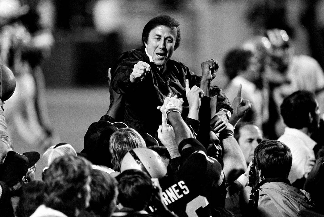 Coach Tom Flores gestures to members of the Los Angeles Raiders as they carry him off the field after their 38-9 victory over the Washington Redskins in Super Bowl XVIII in Tampa Jan. 23, 1984. ( ...