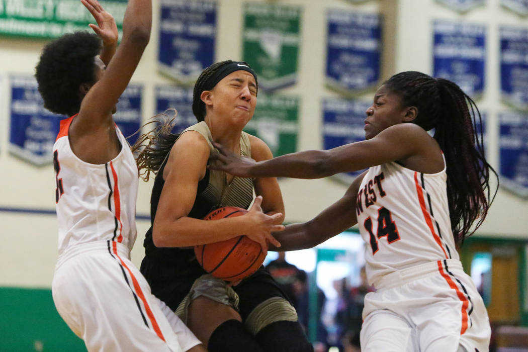 Spring Valley's Garrisen Freeman (32) drives the ball past West Anchorage's Ah'Kayzee Galloway (32), left, and Nyeniea John (14) during the first half of a basketball game at Green Valley High Sch ...