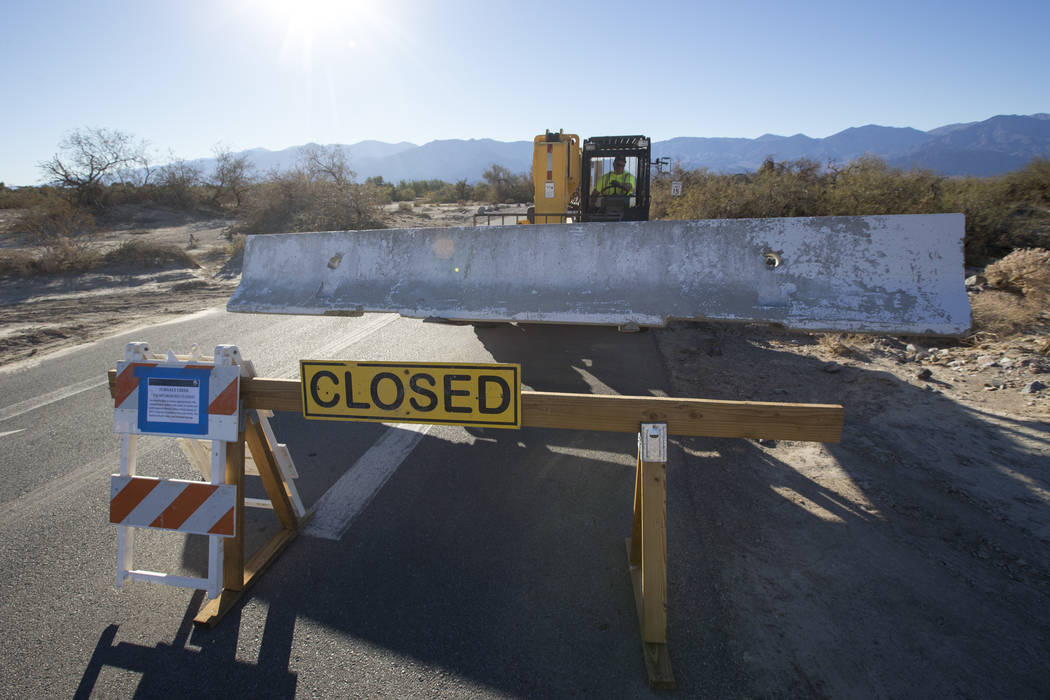 A maintenance worker with the National Park Service sets a jersey barrier to block the entrance to the Furnace Creek Campground after it was closed following health and safety concerns due to lack ...