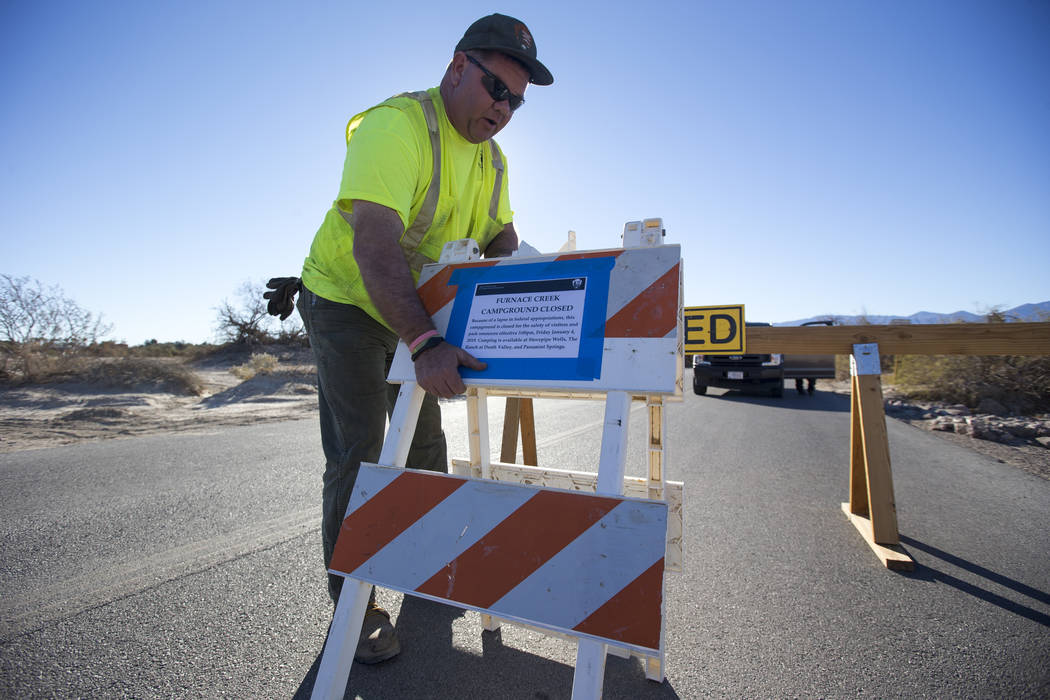 A maintenance worker for the National Park Service posts a sign at the entrance to the Furnace Creek Campground, which was closed following health and safety concerns due to lack of resources duri ...
