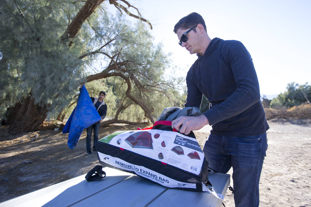 Kevin Randolph, foreground, and Oscar Arroyo pack up their campsite at the Furnace Creek Campground after campers at the site were forced to move following health and safety concerns due to lack o ...