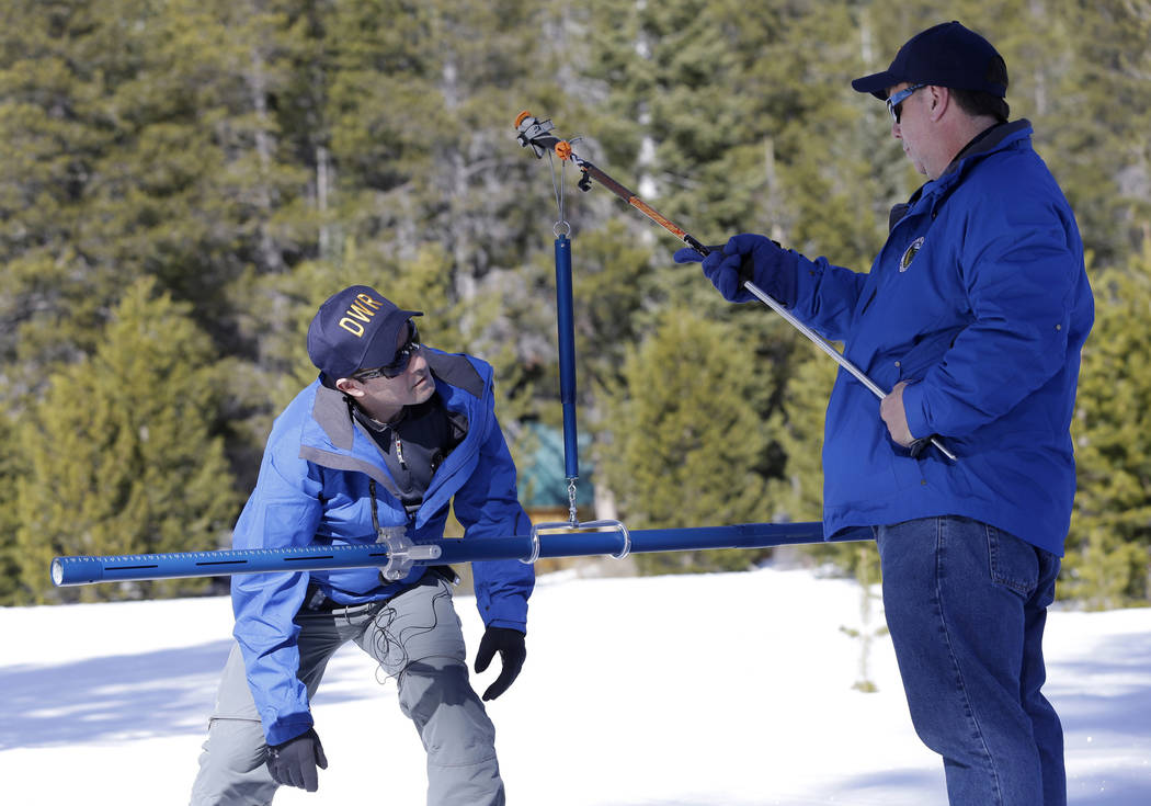 Department of Water Resources Water Resource Engineer John King checks the weight of the snow sample on a scale held by DWR State Climatologist Dr. Michael Anderson, left , during the first snow s ...