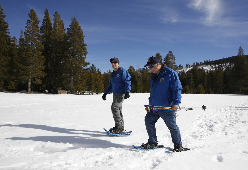 Department of Water Resources Water Resource Engineer John King, left, and DWR State Climatologist Dr. Michael Anderson, right, walk across a snow covered meadow after conducting the first snow su ...